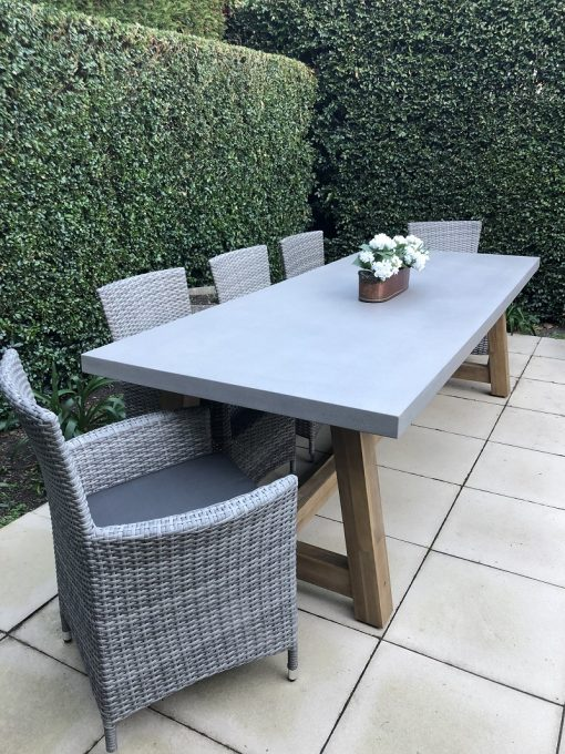 Veltis 8 seater outdoor dining setting with 5 vintage grey wicker chairs with dark grey fabric cushions and a grey topped, wooden based rectangular table- side view