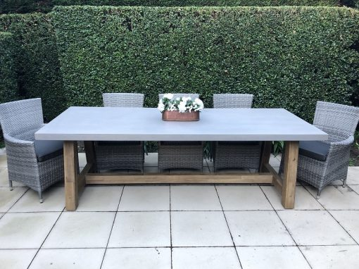 Veltis 8 seater outdoor dining setting with 5 vintage grey wicker chairs with dark grey fabric cushions and a grey topped, wooden based rectangular table